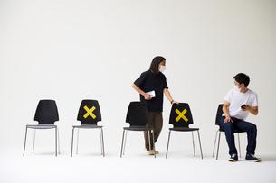 横一列に並んだ椅子に座るマスクをした男性の横に座ろうとして拒絶されるもう一人の男性の写真素材 [FYI04626407]