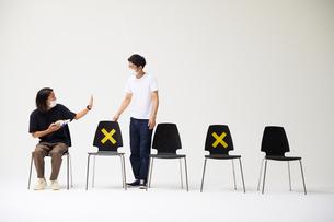 横一列に並んだ椅子に座るマスクをした男性の横に座ろうとして拒絶されるもう一人の男性の写真素材 [FYI04626409]