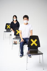 一つおきにバツ印が付いた縦に並ぶ椅子に座る男女                                                               の写真素材 [FYI04626411]