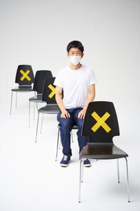 一つおきにバツ印が付いた縦に並ぶ椅子に座る男性                                                              の写真素材 [FYI04626412]