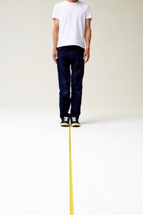 メジャーの上に立つ男性                                                              の写真素材 [FYI04626417]