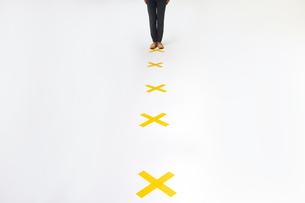 バツ印の上に立つ女性の足元の写真素材 [FYI04626419]