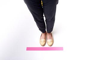 ピンクのテープの上に立つ女性の足元の写真素材 [FYI04626421]