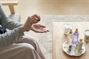 アロマオイルのボトルからオイルを掌に垂らしているソファーに座った女性の手元の写真素材 [FYI04626540]