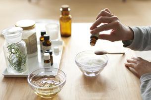 テーブルの上でバスソルト の入ったガラスの器にオイルを垂らしてる女性の手元の写真素材 [FYI04626546]