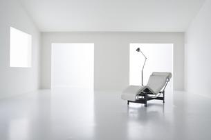 白い空間の中にある椅子とフロアライトの写真素材 [FYI04626677]