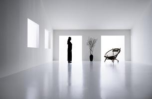 白い空間の中にある椅子と枝が刺さった花器と女性の写真素材 [FYI04626685]