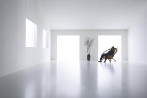 白い空間の中にある男性が座っている椅子の写真素材 [FYI04626686]