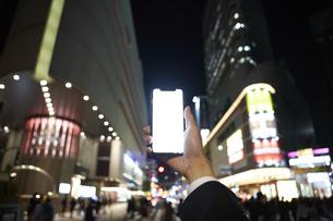 夜の街中でスマートフォンを持ち上げる男性の手元の写真素材 [FYI04626744]