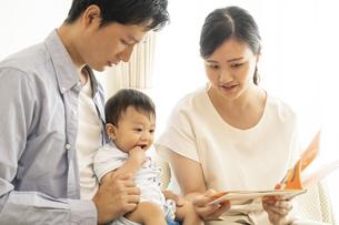 家族に絵本を読んでもらう赤ちゃんの写真素材 [FYI04626935]