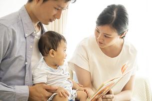 家族に絵本を読んでもらう赤ちゃんの写真素材 [FYI04626936]