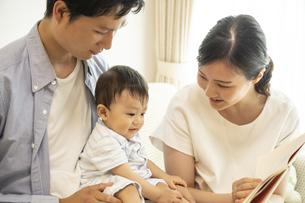 家族に絵本を読んでもらう赤ちゃんの写真素材 [FYI04626938]