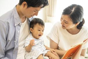 家族に絵本を読んでもらう赤ちゃんの写真素材 [FYI04626939]