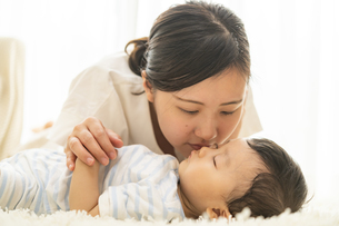 寝ている赤ちゃんにキスをするママの写真素材 [FYI04626958]