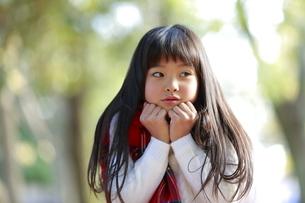 寒そうな仕草のマフラーをつけた少女の写真素材 [FYI04627903]
