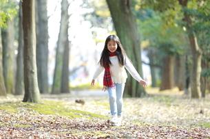 駆け寄る赤いチェック柄のマフラーをつけた少女の写真素材 [FYI04627904]
