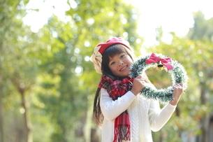 クリスマスリースを持った赤いベレー帽の少女の写真素材 [FYI04627909]