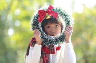 クリスマスリースから覗き込む少女の写真素材 [FYI04627910]