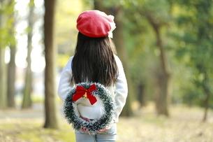 クリスマスリースを持って背を向ける少女の写真素材 [FYI04627912]