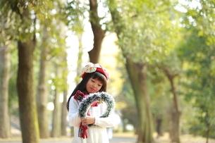 クリスマスリースを持った赤いベレー帽の少女の写真素材 [FYI04627913]