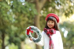 クリスマスリースを持った赤いベレー帽の少女の写真素材 [FYI04627915]