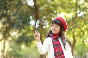 虫眼鏡を覗く赤ベレー帽の少女の写真素材 [FYI04627921]