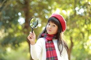 虫眼鏡を持った赤ベレー帽の少女の写真素材 [FYI04627922]