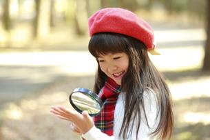 虫眼鏡で自分の手を覗き込む少女の写真素材 [FYI04627923]