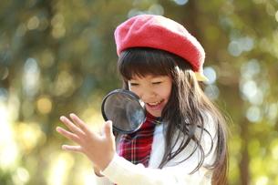 虫眼鏡で自分の手を覗き込む少女の写真素材 [FYI04627924]
