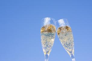 青空をバックに乾杯するシャンパングラスの写真素材 [FYI04628096]