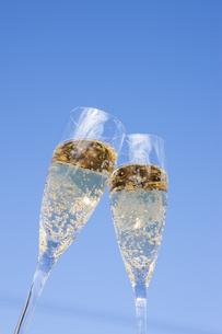 青空をバックに乾杯するシャンパングラスの写真素材 [FYI04628097]