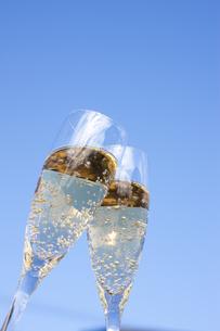 青空をバックに乾杯するシャンパングラスの写真素材 [FYI04628098]
