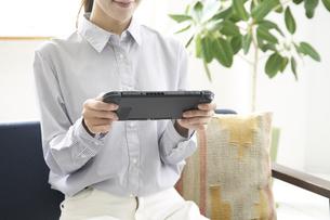 ゲームで遊ぶ若い女性の手元の写真素材 [FYI04628395]