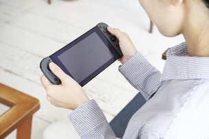 ゲームで遊ぶ若い女性の手元の写真素材 [FYI04628398]