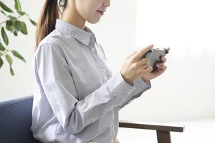 ゲームで遊ぶ若い女性の手元の写真素材 [FYI04628399]