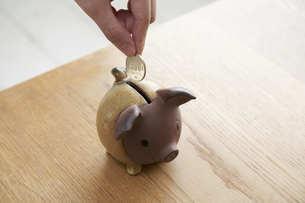 貯金箱に硬貨を入れる女性の手元の写真素材 [FYI04628401]