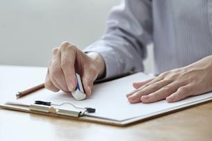 消しゴムで書類の文字を消す女性の手元の写真素材 [FYI04628402]