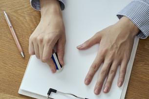 消しゴムで書類の文字を消す女性の手元の写真素材 [FYI04628403]