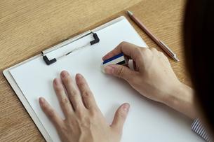 消しゴムで書類の文字を消す女性の手元の写真素材 [FYI04628404]
