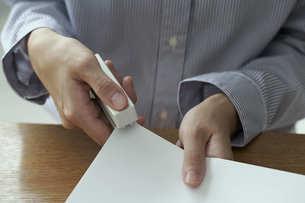 ホチキスで書類をまとめる女性の手元の写真素材 [FYI04628406]