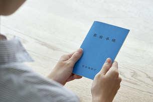 年金手帳を持つ女性の手元の写真素材 [FYI04628411]