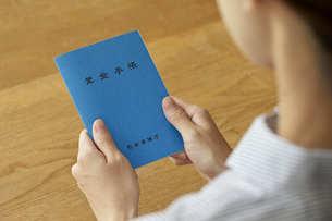 年金手帳を持つ女性の手元の写真素材 [FYI04628412]