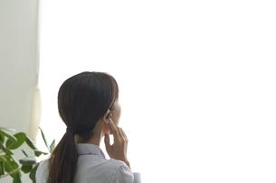 ワイヤレスイヤホンで音楽を聴く若い女性の写真素材 [FYI04628415]