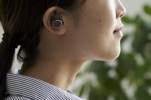 ワイヤレスイヤホンで音楽を聴く若い女性の写真素材 [FYI04628416]