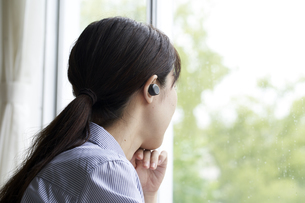 ワイヤレスイヤホンで音楽を聴く若い女性の写真素材 [FYI04628417]