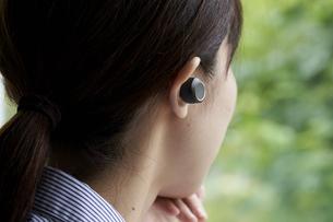 ワイヤレスイヤホンで音楽を聴く若い女性の写真素材 [FYI04628419]