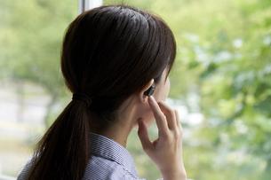 ワイヤレスイヤホンで音楽を聴く若い女性の写真素材 [FYI04628420]