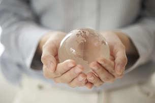 透明の地球儀を持つ女性の手元の写真素材 [FYI04628426]
