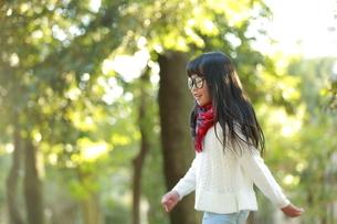 森の中で眼鏡をかけ歩く少女の写真素材 [FYI04628490]