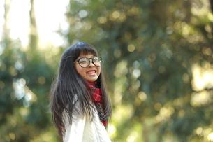 森の中で笑顔でこちらを見る眼鏡の女の子の写真素材 [FYI04628491]